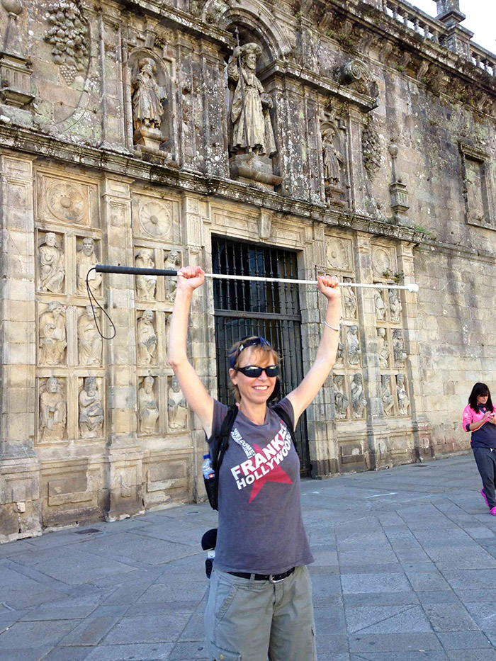 Alex-holds-white-stick-in-the-air-in-front-of-catedral-de-santiago-de-compostela